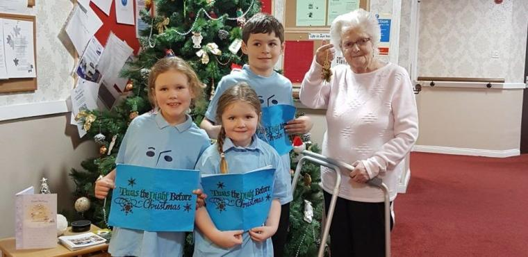 Primary school carol singers perform for care home residents