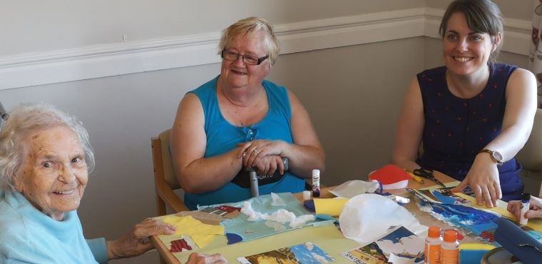 Artrium volunteers get elderly painting their windows