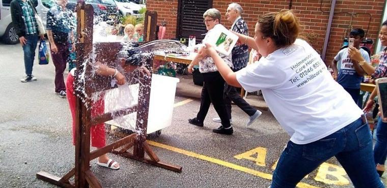 Stocks and a soaking for staff at care home summer fayre