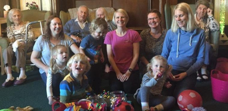 Toddlers and elderly wiggling at care home dance class